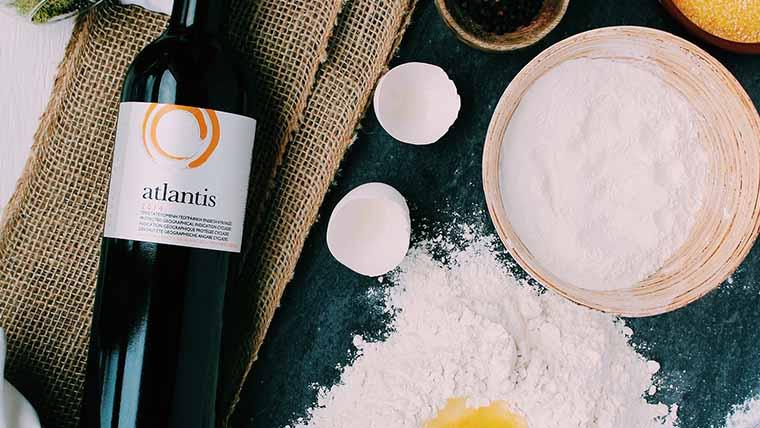 Bottiglia di vino Atlantis accanto a gusci di uova, farina su di una spianatoia