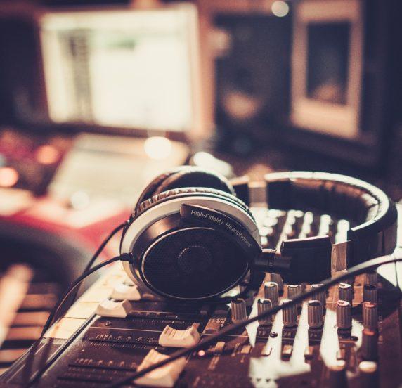 Dettaglio di cuffie audio sopra ad un mixer audio
