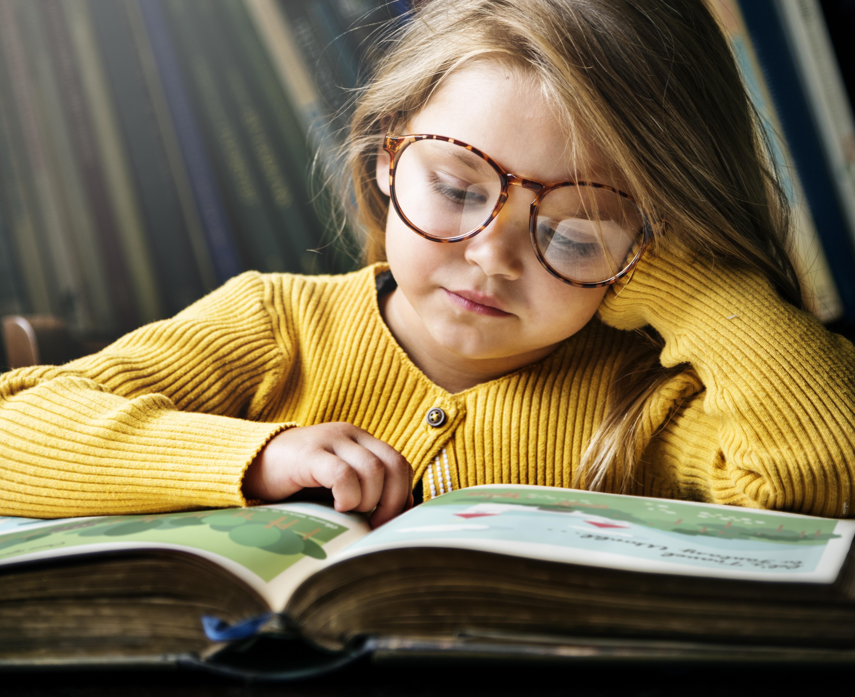 Bambina intenta a leggere un libro